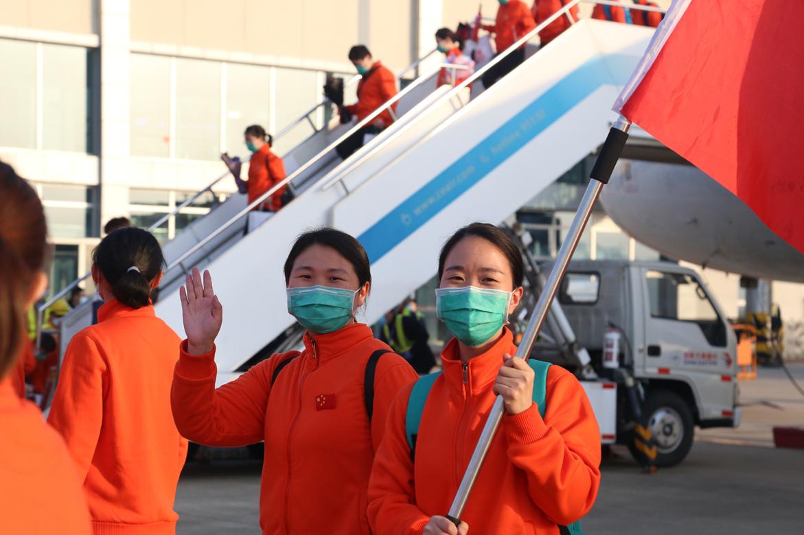 图1:徐丹手举旗帜同江西医疗护理队队员平安返昌