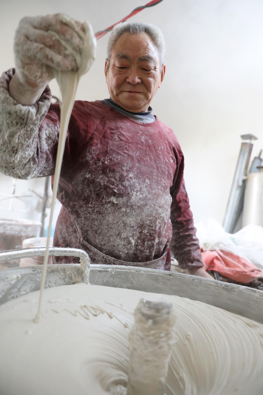 1月13日,河南省焦作市温县黄庄镇南韩村村民在查看和制的粉面准备加工粉条。