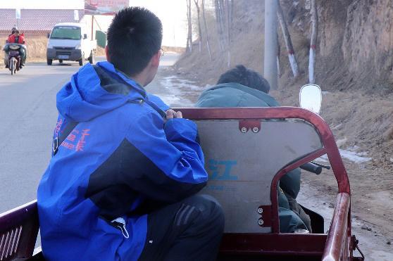 △第二十二届研支团成员在村口乘三轮车去学生家中家访
