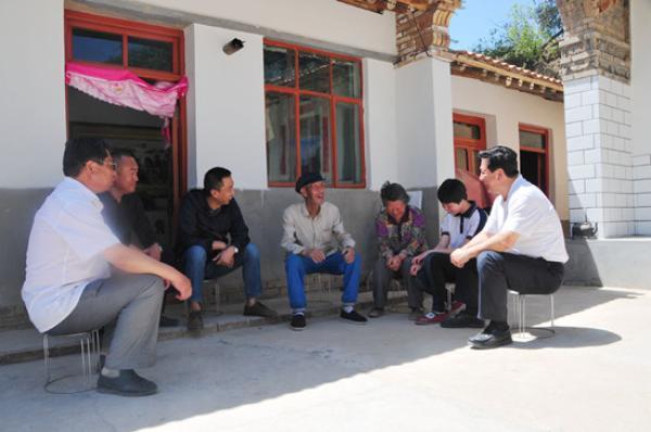 金宝山(右一)在扶贫户老杨家院里走访。