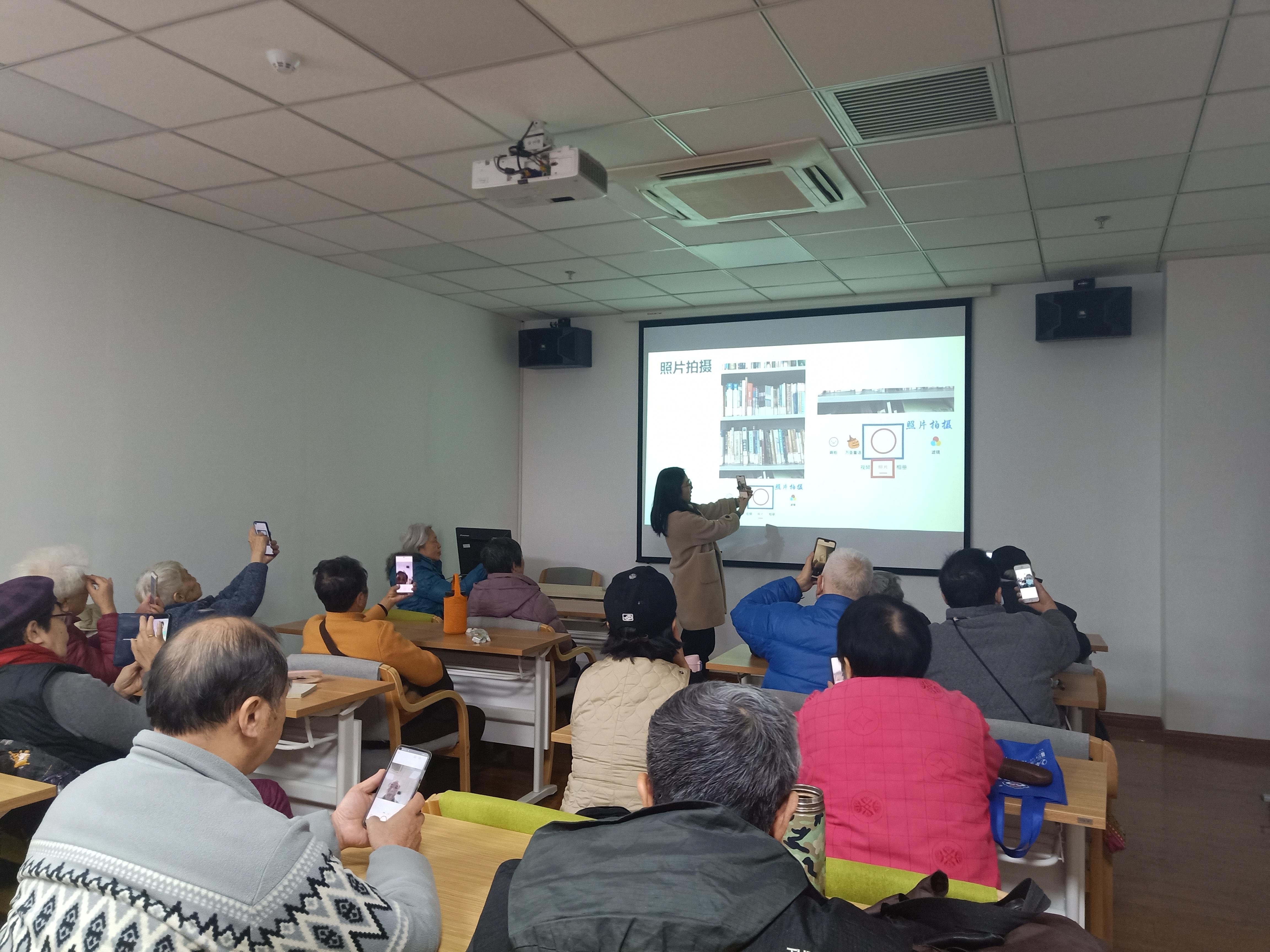 """手机课上,志愿者正在教老人如何拍照(上海师范大学""""智慧老人""""公益服务工作室供图)"""