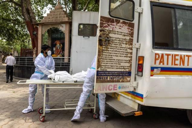 10日,新德里卫生工作者将新冠死亡人员运往火葬场。图源:路透社