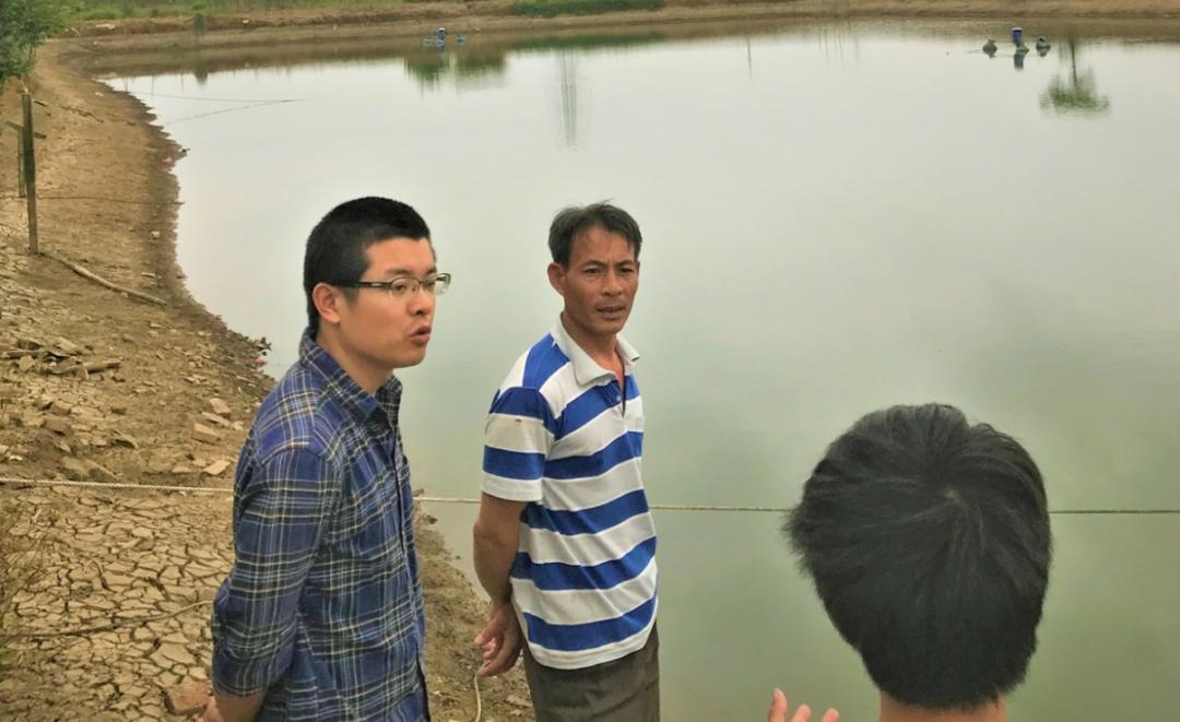 ▲刘小龙(左一)在和养殖户们交流经验