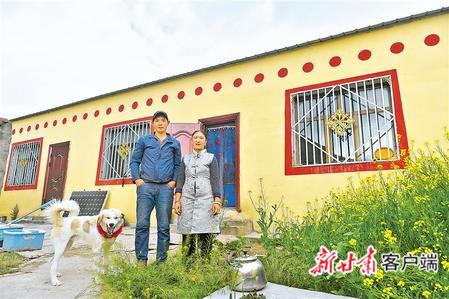 在玉树藏族自治州治多县治渠乡同卡村,村民昂文西让和妻子在易地搬迁的新家院子里合影。