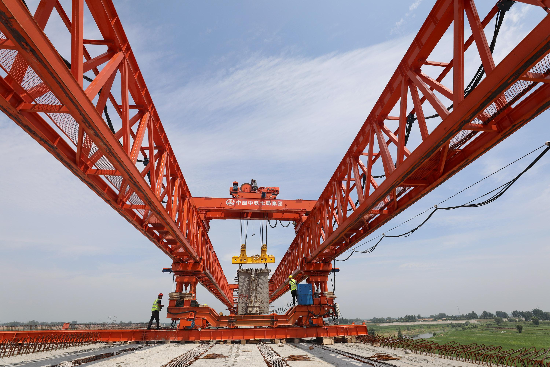 8月3日,建设者们在G207河南焦作至温县快速通道项目沁河特大桥工地架设桥梁。