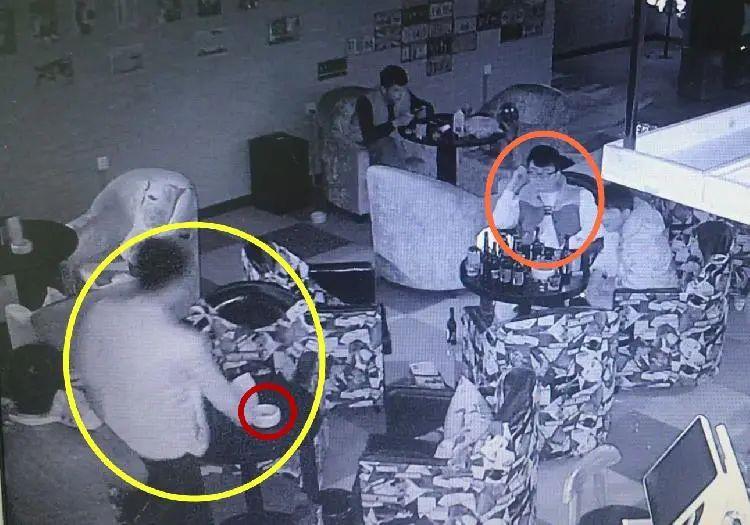 视频监控显示,李雷(黄圈)在伸手拿烟灰缸(红圈),对面是王浪(橙圈)。/视频截屏